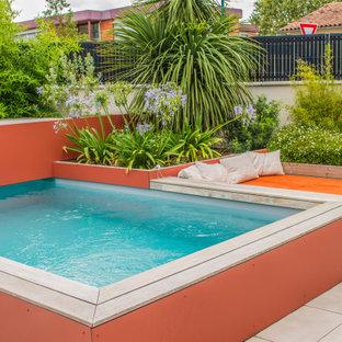 Ejemplo de piscina tropical, pequeña, rectangular, en patio trasero, con suelo de baldosas