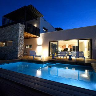 Idee per una grande piscina a sfioro infinito mediterranea rettangolare davanti casa con pedane