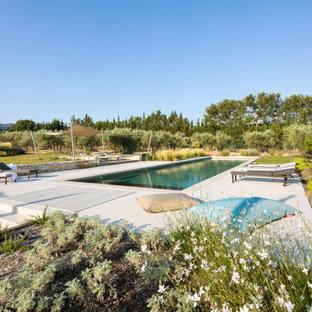 Imagen de piscina mediterránea, grande, rectangular, en patio trasero, con losas de hormigón