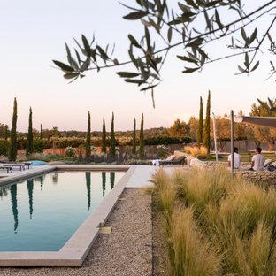 Modelo de piscina mediterránea, grande, rectangular, en patio trasero, con gravilla