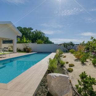 Imagen de piscina alargada, marinera, de tamaño medio, rectangular, en patio delantero, con suelo de baldosas