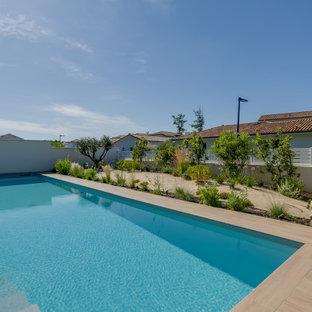 Diseño de piscina alargada, marinera, de tamaño medio, rectangular, en patio delantero, con privacidad y suelo de baldosas