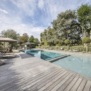 Réalisation d'une très grand piscine méditerranéenne rectangle avec une cour.