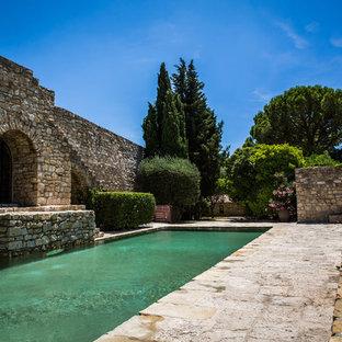 Cette photo montre un couloir de nage arrière chic de taille moyenne et rectangle avec des pavés en pierre naturelle.
