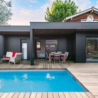 Imagen de piscina escandinava, rectangular, en patio trasero, con entablado