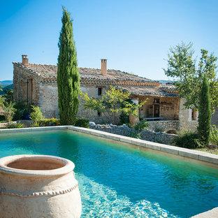 Cette photo montre une piscine arrière méditerranéenne de taille moyenne et rectangle avec des pavés en pierre naturelle.