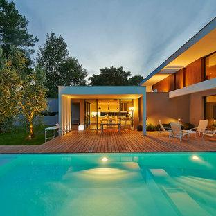Immagine di una grande piscina design rettangolare dietro casa con pedane