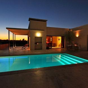 Réalisation d'une grand piscine arrière méditerranéenne rectangle.