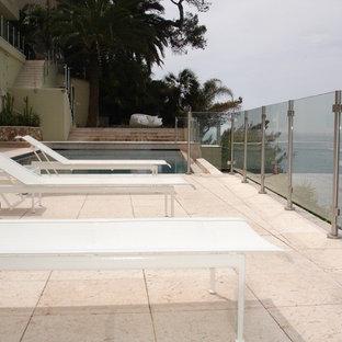 Modelo de casa de la piscina y piscina infinita, actual, a medida, en patio delantero, con adoquines de piedra natural