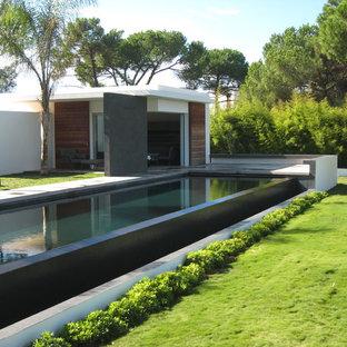 Foto de casa de la piscina y piscina alargada, contemporánea, grande, rectangular, en patio trasero, con losas de hormigón