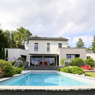 Aménagement d'une grand piscine arrière contemporaine rectangle avec une dalle de béton.