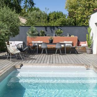 Immagine di una piscina tropicale di medie dimensioni con pedane