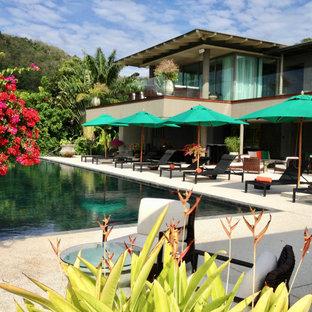 Diseño de piscina de estilo zen, extra grande, rectangular, en patio delantero, con granito descompuesto