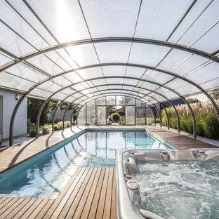 Imagen de casa de la piscina y piscina actual, grande, a medida, en patio trasero, con entablado