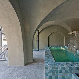 Cette image montre une piscine intérieure méditerranéenne rectangle et de taille moyenne avec des pavés en pierre naturelle.