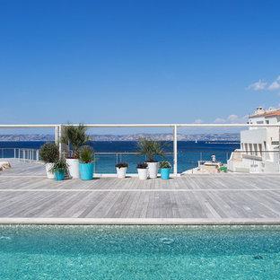 Cette photo montre une grande piscine sur une terrasse en bois arrière bord de mer rectangle.