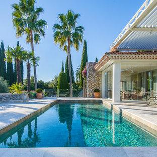 Réalisation d'une grande piscine arrière méditerranéenne rectangle avec des pavés en pierre naturelle.