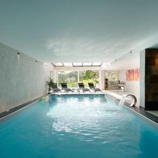 Idée de décoration pour une grand piscine intérieure design rectangle avec un point d'eau et une dalle de béton.