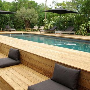 Imagen de piscina alargada, actual, grande, rectangular, con entablado