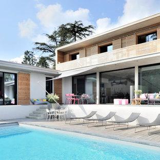 Réalisation d'une piscine sur une terrasse en bois arrière design rectangle et de taille moyenne.