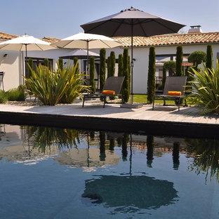 Aménagement d'une piscine sur une terrasse en bois arrière méditerranéenne rectangle et de taille moyenne.