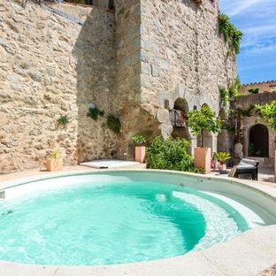 Foto de piscinas y jacuzzis eclécticos, pequeños, redondeados, en patio, con adoquines de piedra natural