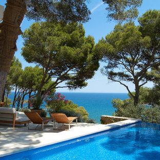 Imagen de casa de la piscina y piscina infinita, marinera, de tamaño medio, rectangular, en patio trasero, con losas de hormigón