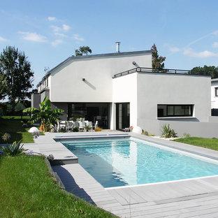 Idée de décoration pour une piscine arrière design de taille moyenne et rectangle avec un bain bouillonnant.