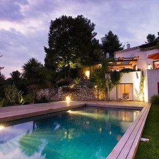 Inspiration pour une grand piscine sur une terrasse en bois arrière méditerranéenne rectangle.