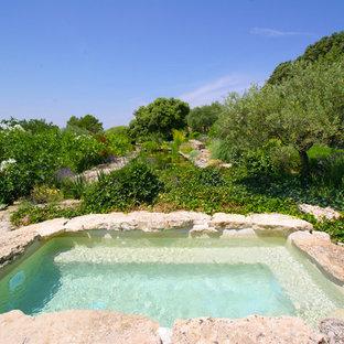 Aménagement d'une piscine méditerranéenne rectangle avec un bain bouillonnant et des pavés en pierre naturelle.