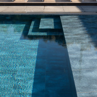 Immagine di una grande piscina minimal rettangolare dietro casa con pedane