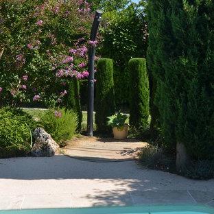 Imagen de piscina actual, grande, tipo riñón, en patio delantero, con granito descompuesto
