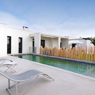 Cette photo montre un couloir de nage arrière moderne rectangle et de taille moyenne avec une dalle de béton.
