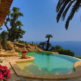 Inspiration pour une piscine à débordement et arrière méditerranéenne de taille moyenne et sur mesure avec un bain bouillonnant et des pavés en pierre naturelle.