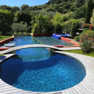 Réalisation d'une grand piscine sur une terrasse en bois arrière design sur mesure avec un bain bouillonnant.