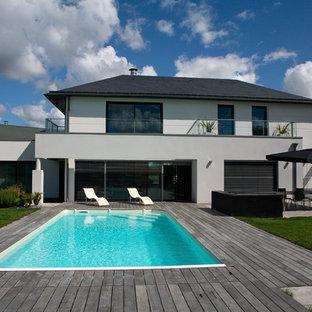 Foto de piscina urbana, de tamaño medio, rectangular, en patio trasero, con entablado