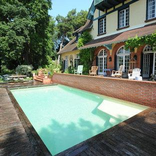 Cette photo montre une piscine sur une terrasse en bois arrière nature de taille moyenne et rectangle.