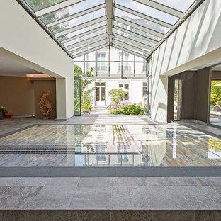 Idée de décoration pour une grand piscine intérieure design rectangle avec des pavés en pierre naturelle.