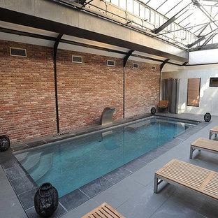 Ejemplo de piscina con fuente industrial, grande, rectangular y interior, con suelo de baldosas