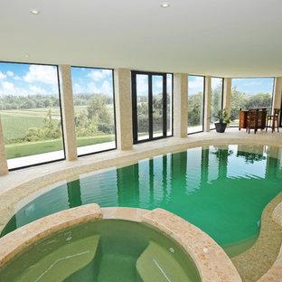 Idées déco pour une piscine intérieure méditerranéenne en forme de haricot de taille moyenne avec un bain bouillonnant et des pavés en pierre naturelle.