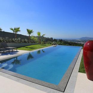 Réalisation d'une grand piscine à débordement et arrière design rectangle avec des pavés en pierre naturelle.