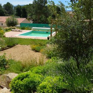Ejemplo de piscina mediterránea, grande, rectangular, en patio delantero, con granito descompuesto