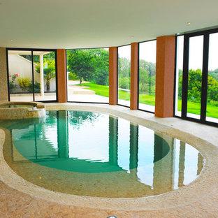 Idée de décoration pour une piscine intérieure méditerranéenne en forme de haricot avec un bain bouillonnant.
