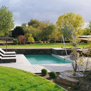 Idée de décoration pour une piscine sur une terrasse en bois arrière champêtre rectangle et de taille moyenne.