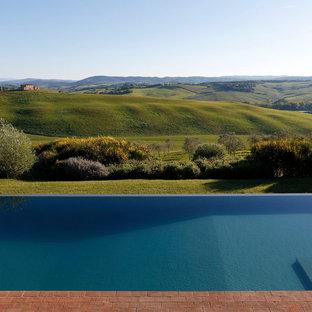 Immagine di una piscina a sfioro infinito moderna rettangolare dietro casa con pavimentazioni in mattoni
