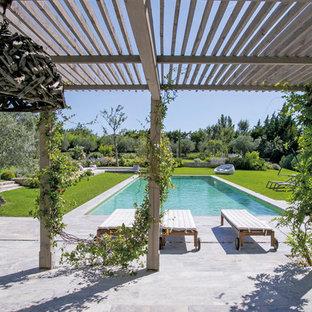 Immagine di un'ampia piscina country rettangolare dietro casa con piastrelle