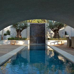 Immagine di una grande piscina monocorsia minimal rettangolare dietro casa con fontane e pedane