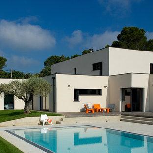 Imagen de piscina actual, rectangular, en patio delantero, con losas de hormigón