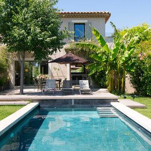 Imagen de piscina tropical, rectangular, en patio delantero, con entablado