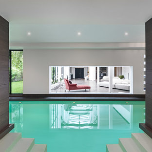 Réalisation d'une grand piscine design rectangle avec du carrelage.
